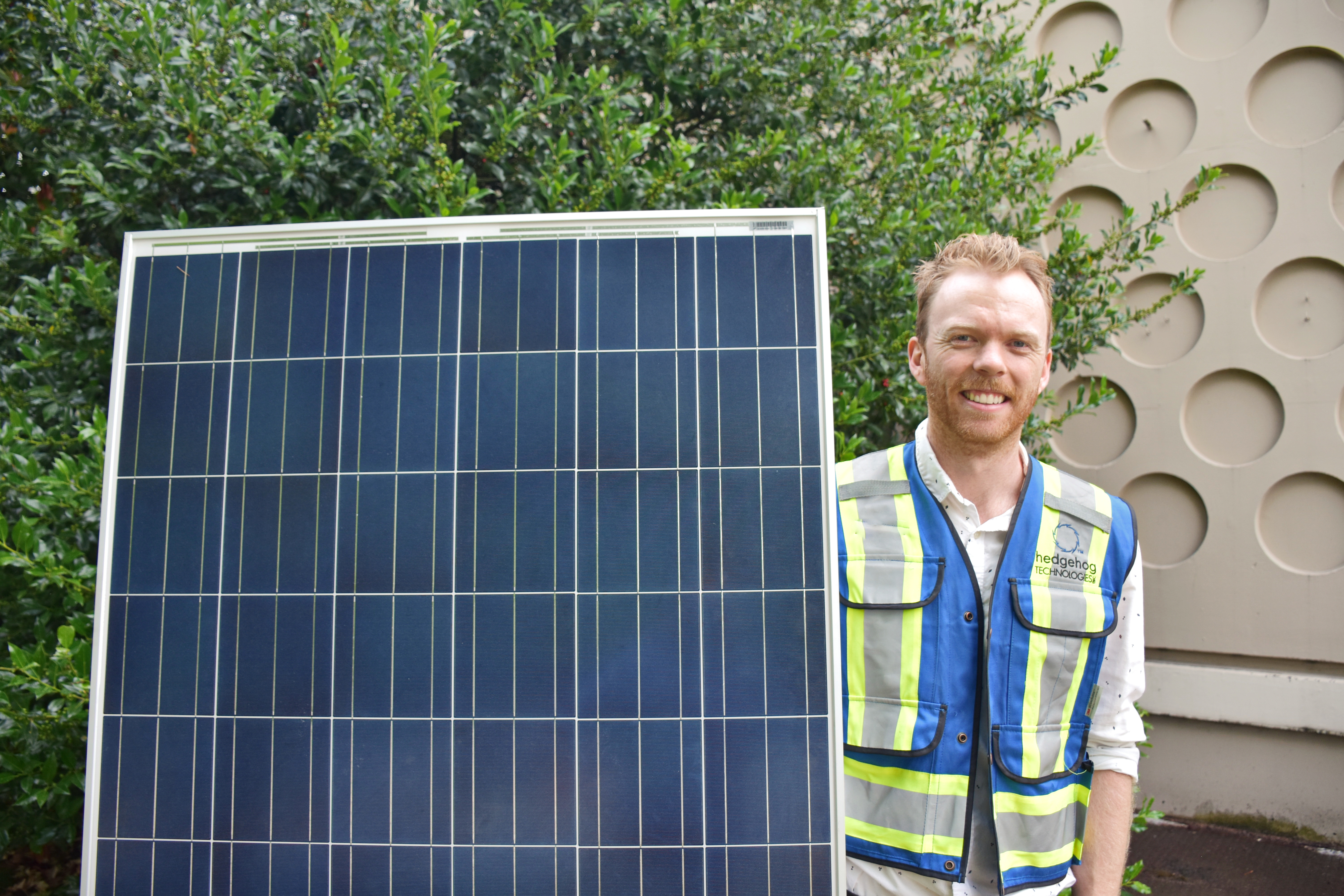 A co-op engineer holding a solar panel